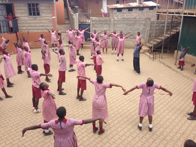 Festus leads exercises for the kids before their exams to help them relax.